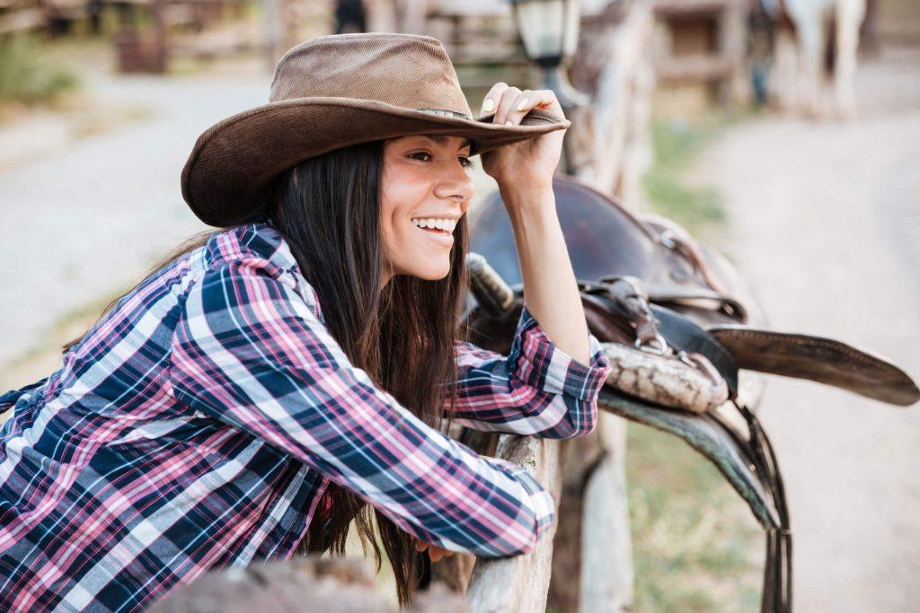Western Style - Cowgirl mit Cowboyhut, Karobluse, auf Pfosten gelehnt